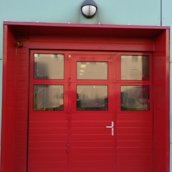 Porte sectionnelle industrielle avec portillon intégré DUNKERQUE